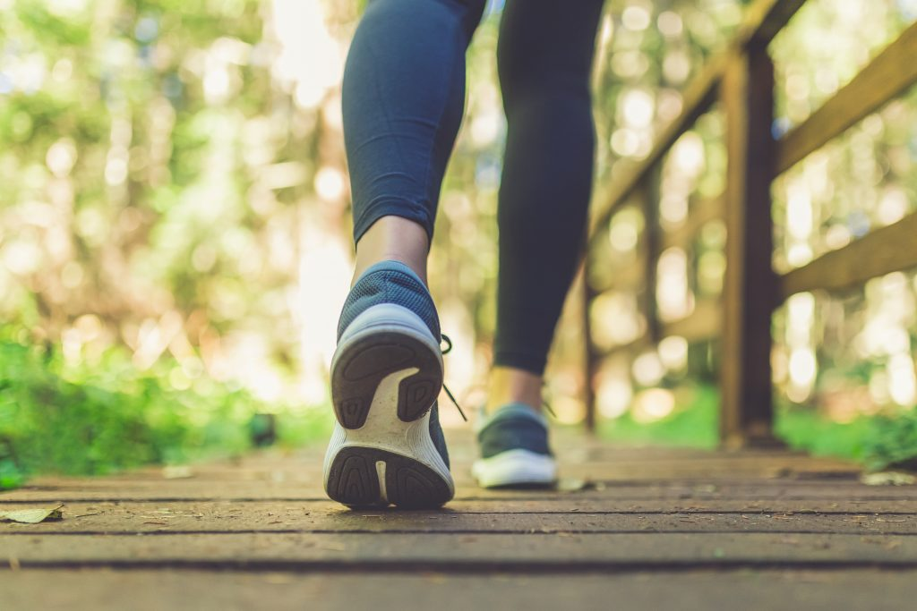 Close up of female legs with running shoes on wooden footpath in woods. Enjoying extra daylight by adding a short walk.